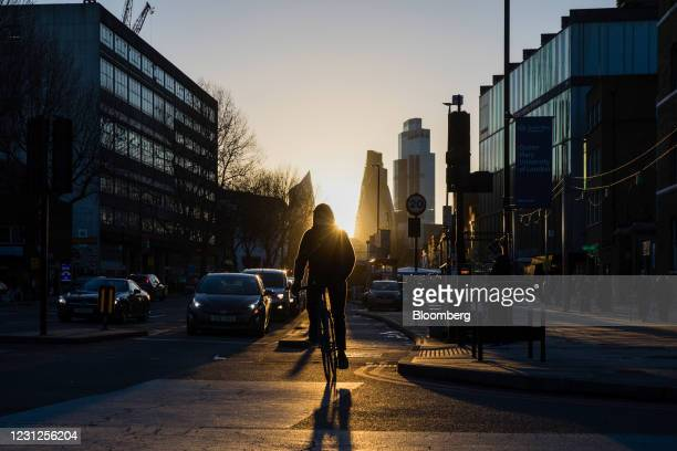 Cyclist on the Mile End Road against a backdrop of skyscrapers in the City of London square mile financial district in London, U.K., on Thursday,...