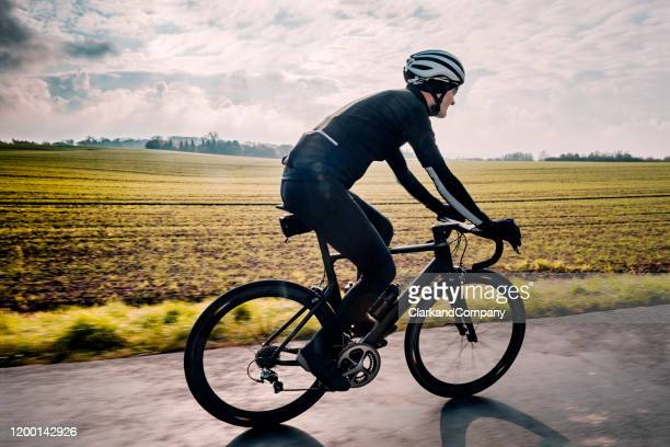 cyclist out for a winter training ride in denmark. - road cycling stock pictures, royalty-free photos & images
