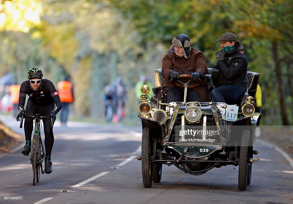 A cyclist overtakes a 1902 Panhard et Levassor as it takes part in the 120th London to Brighton Veteran Car Run on November 6, 2016 in Staplefield, England. Over 400 pre-1905 manufactured vehicles take part in the annual run from London to Brighton to commemorate the Emancipation Run of November 1896 which celebrated the raising of the speed limit from 4mph to 14 mph.