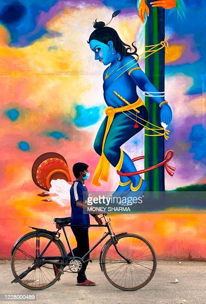 A cyclist pass by a graffiti of Hindu God Krishna in Noida on August 11 2020 on the eve of the 'Janmashtami' festival which marks the birth of the...