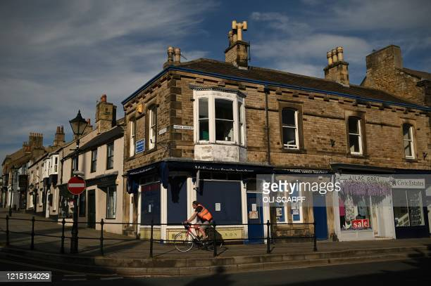 A cyclist passes a closed down shop in Barnard Castle less than 30 miles southwest of Durham north east England on May 25 a popular tourist village...