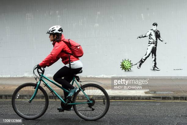 Cyclist passes a Coronavirus-inspired piece of graffiti in Glasgow on April 4 as life in Britain continues during the nationwide lockdown to combat...