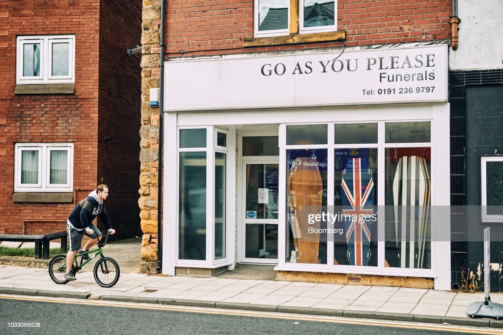 A cyclist passes a funeral directors store displaying coffins featuring different designs, including one in the style of a Union flag, also known as the Union Jack, in Wallsend, U.K., on Thursday, Sept. 6, 2018. The northeast of England illustrates the precarious position facing many parts of the U.K. just six months before the country is due to leave the EU. Photographer: Matthew Lloyd/Bloomberg via Getty Images