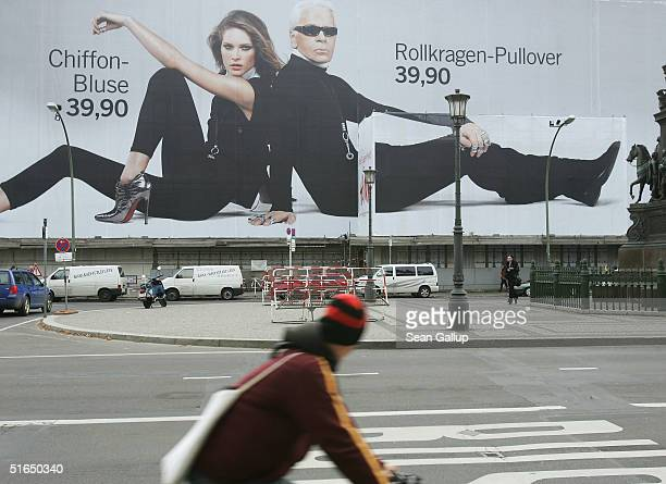 Cyclist passes a giant 1,500 square meter advertisement for Swedish fashion retailer H&M that shows German-born fashion designer Karl Lagerfeld and...