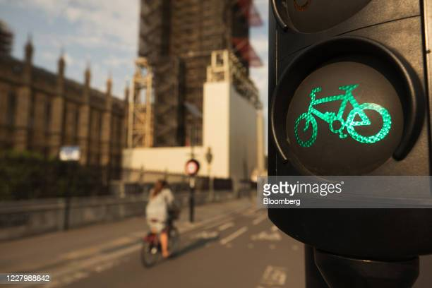 Cyclist passes a green bicycle traffic light on a section of the Cycle Superhighway operated by Transport for London near the Houses of Parliament in...