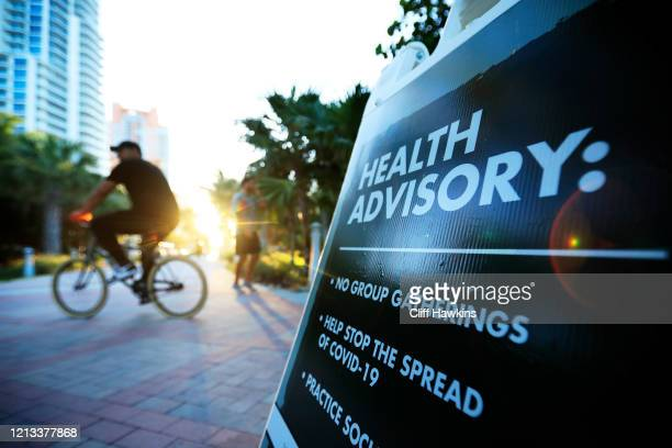 A cyclist passes a Health Advisory sign on March 18 2020 in Miami Beach Florida Miami Beach city officials closed the area of the beach that is...