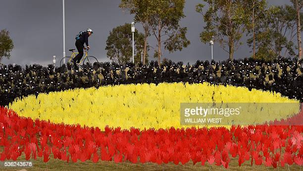 A cyclist passes a huge art installation called 'Sea of Hands' which consists of thousands of hands in the colours of the Aboriginal flag red yellow...