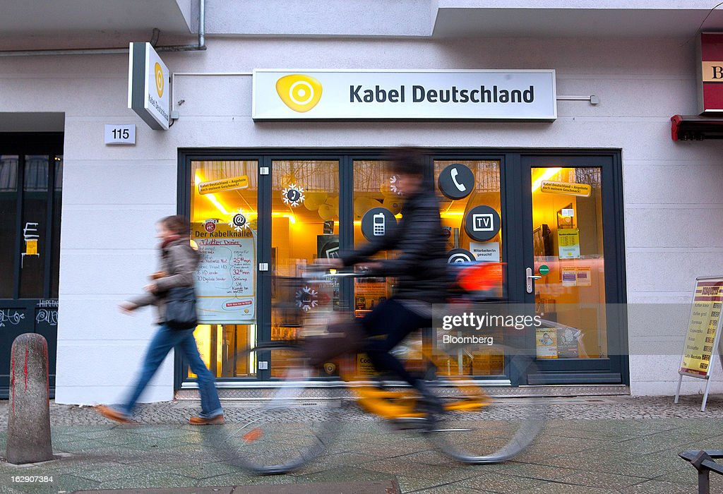 A cyclist passes a Kabel Deutschland store, operated by Kabel Deutschland Holding AG, the German cable operator in Berlin, Germany, on Friday, March 1, 2013. Vodafone Group Plc has put on hold plans to approach Kabel Deutschland Holding AG about a takeover bid after leaks of a potential offer complicated internal discussions, according to three people familiar with the matter. Photographer: Krisztian Bocsi/Bloomberg via Getty Images