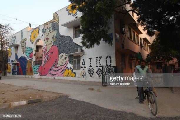 A cyclist passes a mural by Japanese artist Aiko in the open air gallery at Lodhi Colony in New Delhi India 14 February 2016 More than 25 artists...