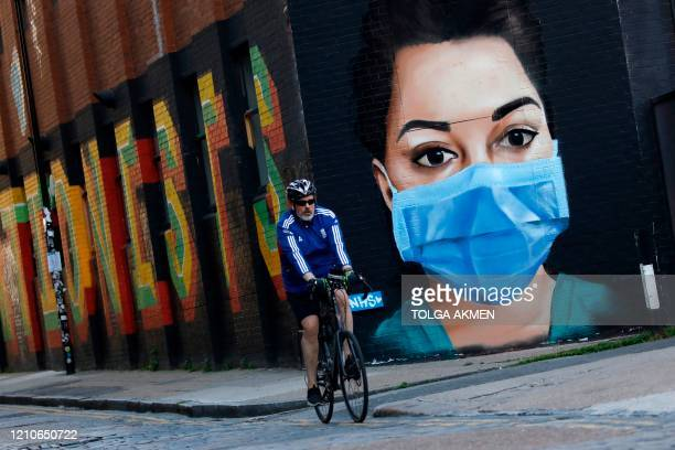 A cyclist passes a mural of an NHS worker in central London as Britain remains under lockdown during the coronavirus crisis on April 22 2020 The new...