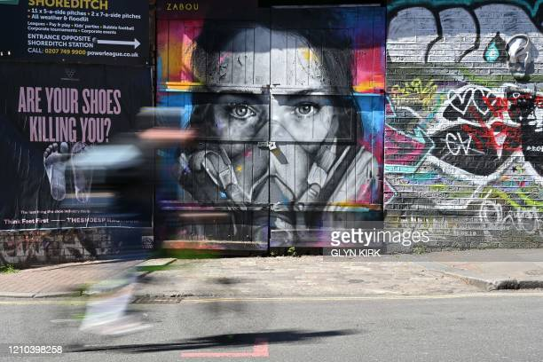 TOPSHOT A cyclist passes a piece of graffiti of artist BK Foxx wearing her graffiti mask created by French street artist Zabou in East London on...