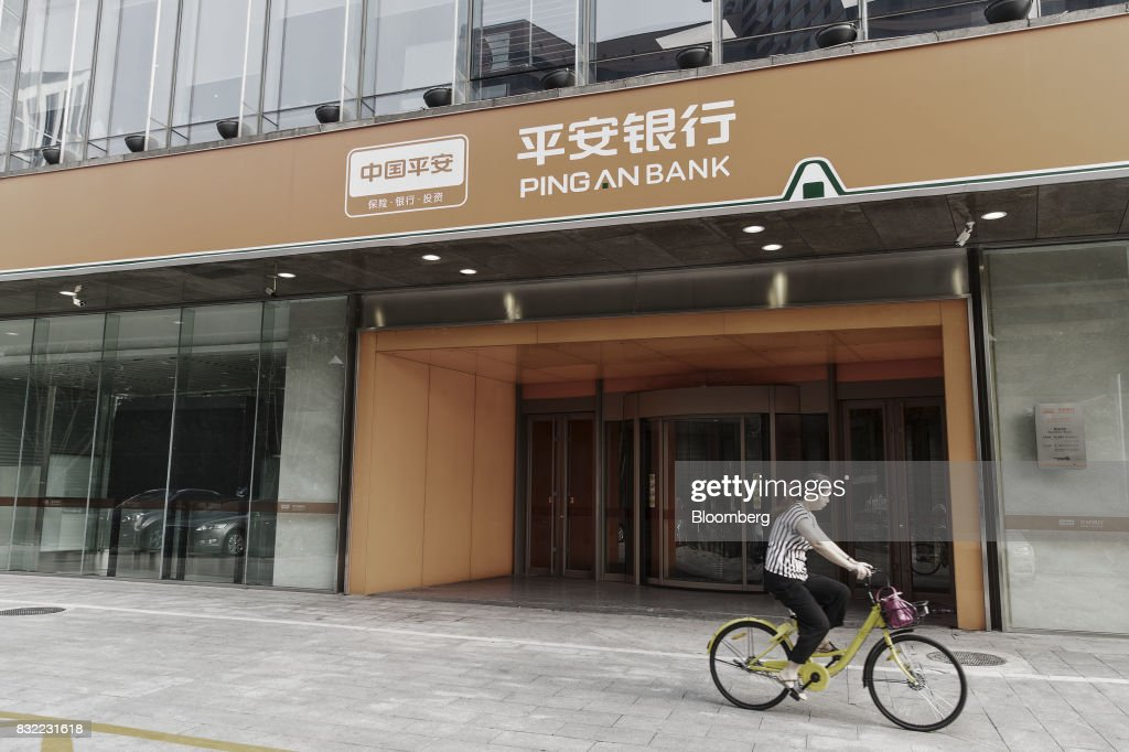 A cyclist passes a Ping An Bank Co. branch, a unit of Ping An Insurance Group Co., in Beijing, China, on Wednesday, Aug. 9 2017. Ping An Insurance Group is scheduled to release half year results on Aug. 17. Photographer: Qilai Shen/Bloomberg via Getty Images