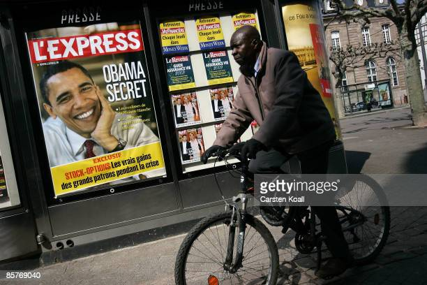 A cyclist passes a press shop showing a big poster of USPresident Barack Obama who will attend the NATO Summit on April 2 2009 in Strasbourg France...