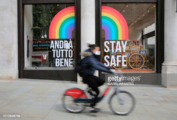 Cyclist passes a shop window with a rainbow symbol of hope and the message to 'Stay Safe' in central London on May 13, 2020 as the coronavirus...