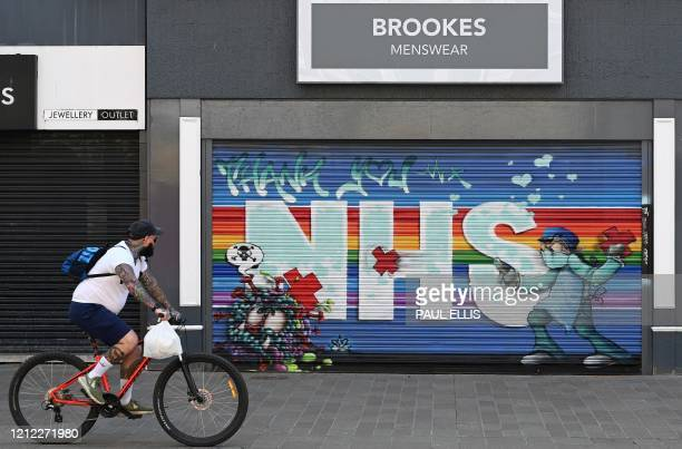 Cyclist passes a street art graffiti mural in support of the NHS on the shutters of a closed-down shop in Hull, northern England on May 9 as life in...