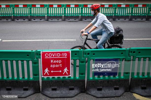 Cyclist passes along Oxford Street where barriers have been installed to widen the pavement to enable social distancing on June 12, 2020 in London,...