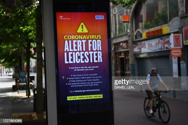 A cyclist passes an electronic billboard with a government message informing the public of local lockdown conditions in the centre of Leicester...