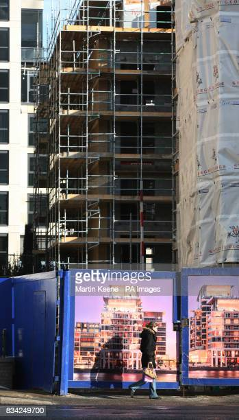 A cyclist passes an entrance for construction vehicles to Imperial Wharf a mixed development by St George PLC on the banks of the Thames next to...