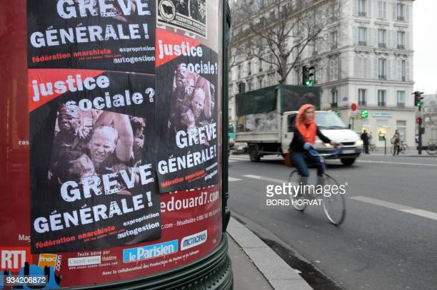 A cyclist passes by a board from Anarchist Federation calling to general strike on January 29 2009 in Paris during France's first major strike...