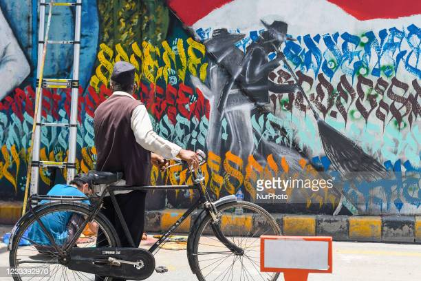 Cyclist passes by as the artists painta wall to show respect and gratitude to the frontline workers and to raise awarenessabout COVID-19 in...