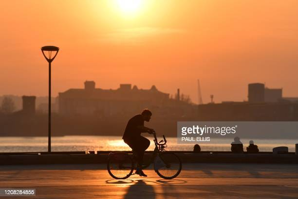 Cyclist passes by as the sun sets on Liverpool Pier Head in Liverpool, north-west England on March 26, 2020.