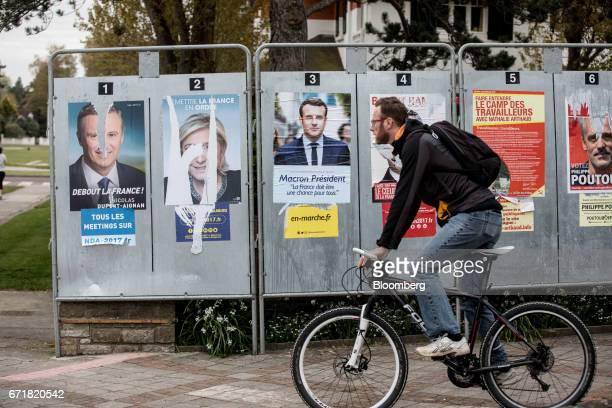 A cyclist passes by electoral campaign posters during the first round of the French presidential election in Le Touquet France on Sunday April 23...