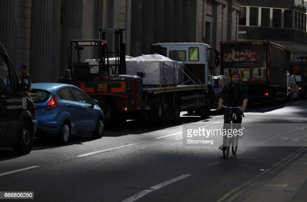 A cyclist passes by vehicles waiting in traffic in London UK on Monday April 10 2017 London has missed by seven years legal deadlines to improve air...
