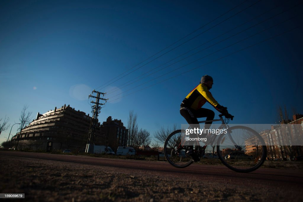 A cyclist passes electricity power lines near residential buildings in Madrid, Spain, on Sunday, Jan. 6, 2013. In December, the Spanish parliament passed an energy law that imposed a 7 percent tax on electricity generation from Jan. 1 to plug the deficit. Photographer: Angel Navarrete/Bloomberg via Getty Images