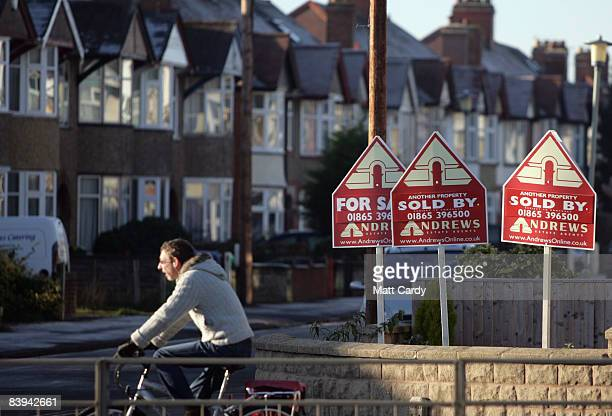 A cyclist passes estate agents property sold signs outside the Mini Plant Oxford as a skeleton staff prepare the factory for an extended closure on...