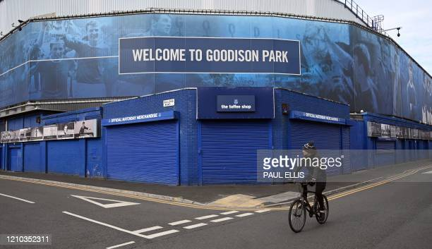 A cyclist passes Everton football club's stadium Goodison Park in Liverpool northwest England on April 18 2020 Premier League clubs remain committed...