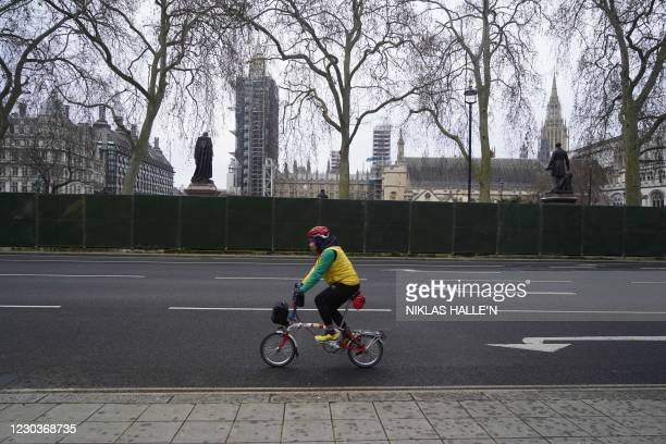 Cyclist passes fencing in Parliament Square outside the Houses of Parliament in central London on December 31, 2020 ahead of the turning of the New...