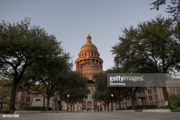 A cyclist passes in front of the Texas State Capitol building in Austin Texas US on Tuesday March 14 2017 Austin has spent the last 10 monthsengaged...