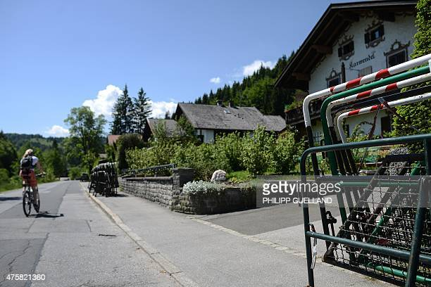 Cyclist passes mobile barriers stacked on a sidewalk near Elmau castle during preparation for G7-summit on June 4, 2015 in Klais near Kruen, southern...