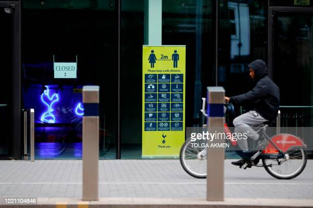 Cyclist passes signs giving information on social distancing outside the ground ahead of the English Premier League football match between Tottenham...