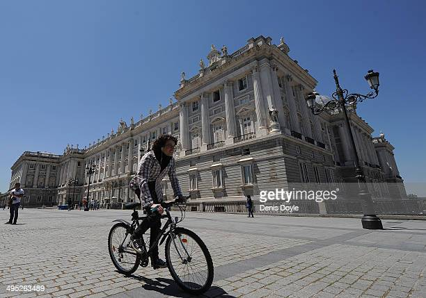 A cyclist passes Spain's Royal Palace on June 2 2014 in Madrid Spain King Juan Carlos of Spain has renounced the throne after 39 years and will be...