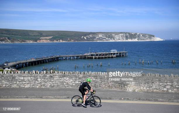 Cyclist passes Swanage pier and coastline on April 15, 2020 in Swanage, United Kingdom. The Coronavirus pandemic has spread to many countries across...