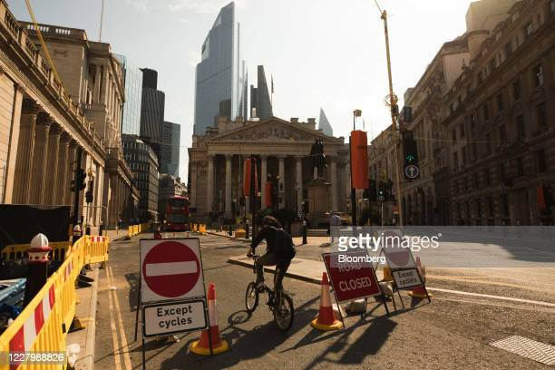 A cyclist passes temporary bike lane signs outside the Bank of England left in The City of London UK on Monday Aug 10 2020 With a budget of £2...