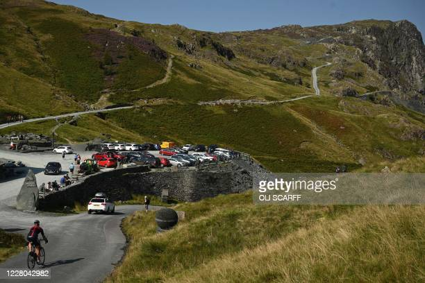 Cyclist passes the car park at the slate mine on Honister Pass in the Lake District in north west England on August 14 as many people take advantage...