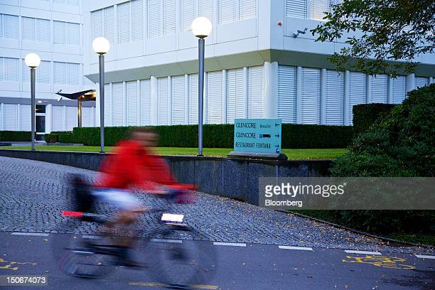 Cyclist passes the entrance to Glencore International Plc's headquarters in Baar, Switzerland, on Friday, Aug. 24, 2012. Glencore's planned takeover...