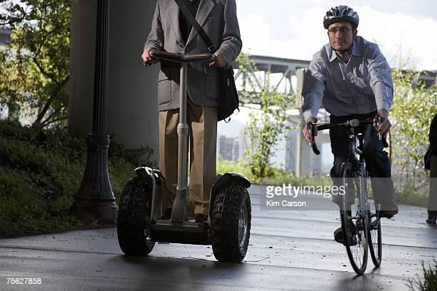 Cyclist passing man riding segway on path