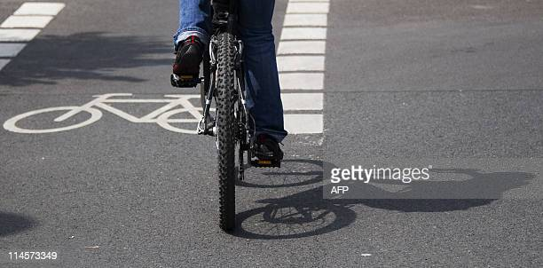 A cyclist pedals along a dedicated bike lane in central Berlin on May 18 2011 Bicycles are a much used way of travel around the mainly flat German...