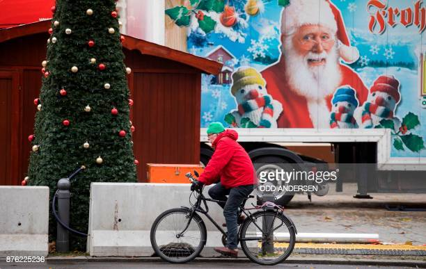 A cyclist pedals past concrete barriers surrounding the Christmas market at Breitscheidplatz in central Berlin on November 192017 Berlin Christmas...