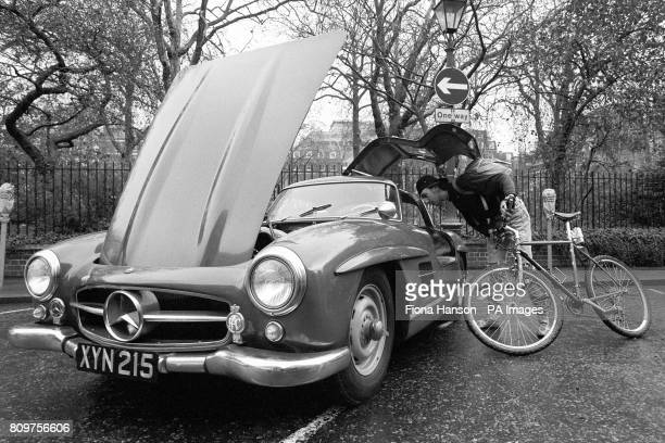 Cyclist Peter Knight takes a look inside a 1955 MercedesBenz 300SL Lightweight Gullwing Coupe during a preview in St James' Square London of classic...