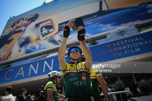 TOPSHOT A cyclist poses for selfies outside the Festival Palace on May 17 2018 during the 71st edition of the Cannes Film Festival in Cannes southern...