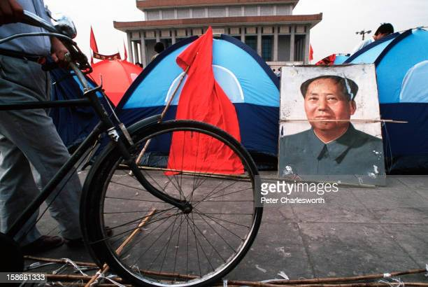 Cyclist pushes a bicycle past a portrait of Mao Tsetung standing outside tents being used by pro-democracy demonstrators who are camping in Tiananmen...