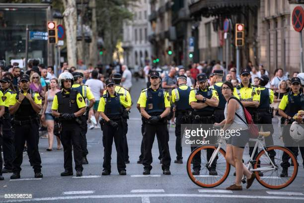 A cyclist pushes her bike past a line of police officers on Las Ramblas near the scene of yesterday's terrorist attack on August 18 2017 in Barcelona...