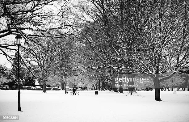 A cyclist pushes their bike through snow in Abington park in Northampton after much of Britain received another blanket of snow on January 6 2010 in...