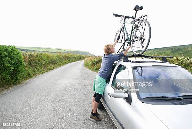 Cyclist putting bicycle on roof of car.