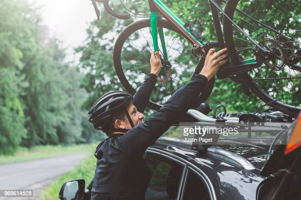cyclist putting bike on car roof rack - sportswear stock pictures, royalty-free photos & images