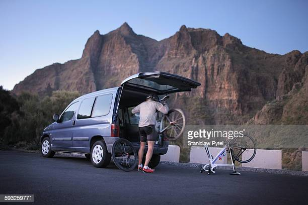 Cyclist putting his bicycle to car after workout